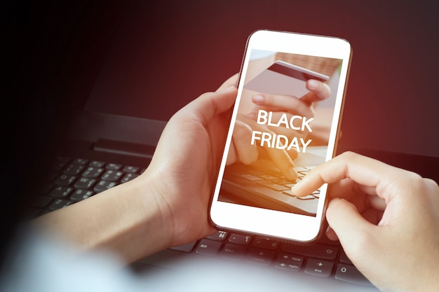Приложение для покупок в черную пятницу на экране мобильного телефона, в то время как улыбающаяся женщина держит его в руке