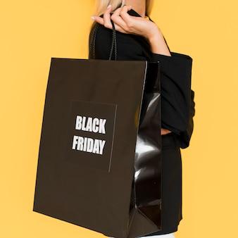 女性によって開催されている黒い金曜日の買い物袋