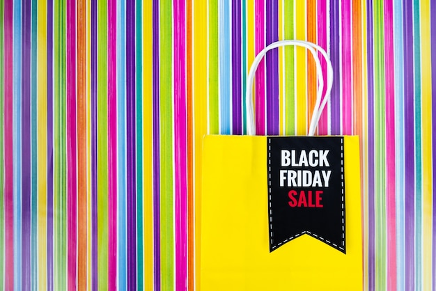 Black friday shopping bag on colorful background