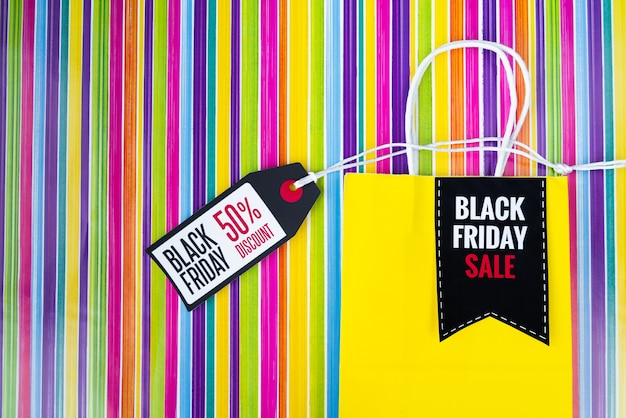 Black friday shopping bag with tag on colorful background