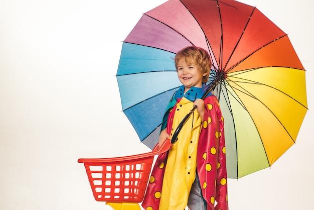 ブラックフライデーの買い物。幸せなかわいい賢い男の子。色の傘を持つ子供。オンライン広告。楽しんでいる3〜5歳の幸せな子供の男の子。あなたのロゴ。