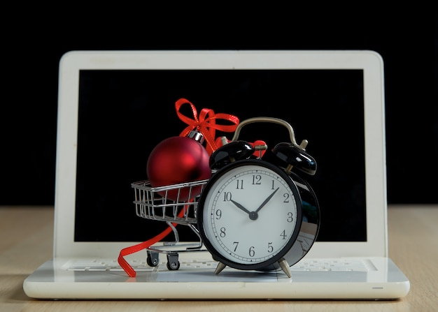 Black friday shopping and retail concept. shopping trolley cart laptop and red christmas ball with a bow on wooden table with a black background. online supermarket marketing or buying concept.