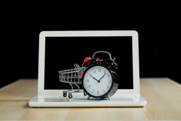 Black friday shopping and retail concept. shopping trolley cart laptop with a clock on wooden table with a black background. online supermarket marketing or buying concept.