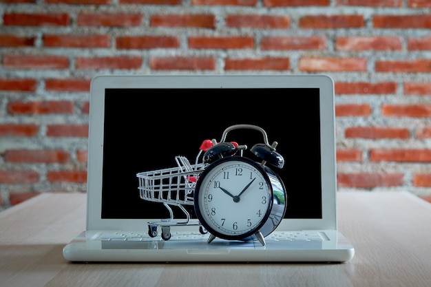 Black friday shopping and retail concept. shopping trolley cart laptop with a clock on wooden table with a red brick wall. online supermarket marketing or buying concept.