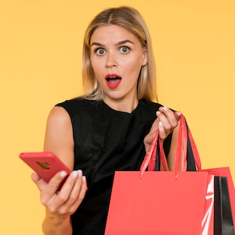 Black friday shopping surprised woman with mobile phone