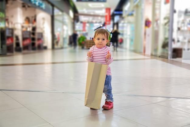 검은 금요일 아이들과 쇼핑하는 귀여운 여자아이는 쇼핑을 위해 종이 가방을 들고 교활하게 웃는다