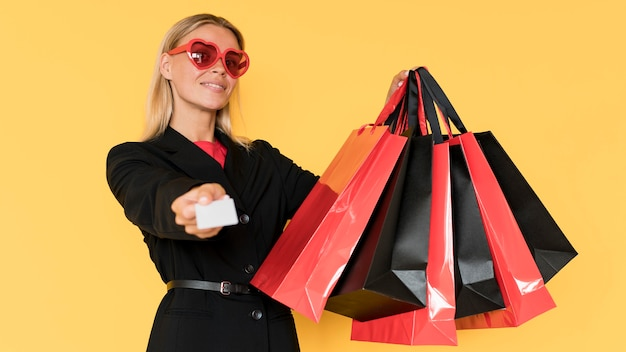 Black friday shopping woman showing bags and voucher