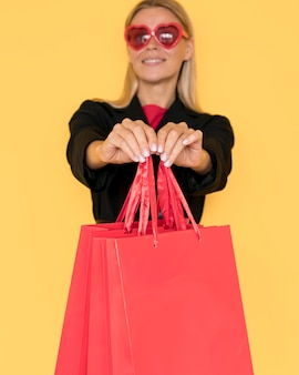 Black friday shopping woman showing red bags