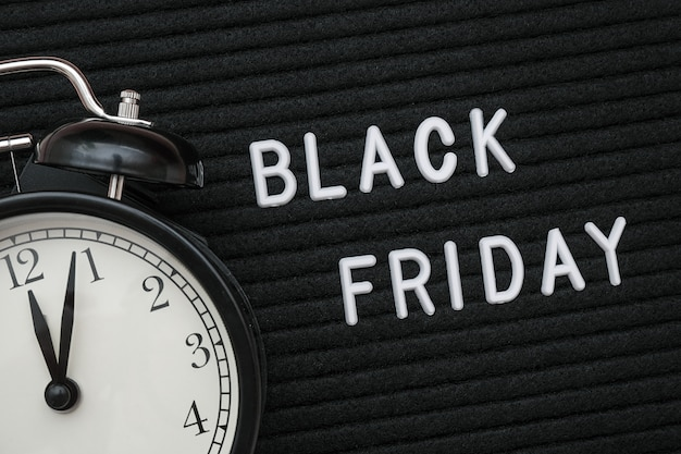 Black friday text on black letterboard and alarm clock