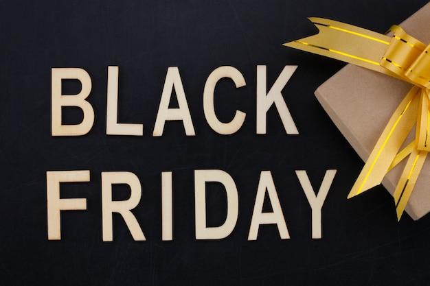 블랙 프라이데이 - 선물이 있는 칠판에 나무 글자로 된 텍스트. 공간을 복사합니다.