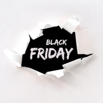 Black friday text in paper hole teared in white paper