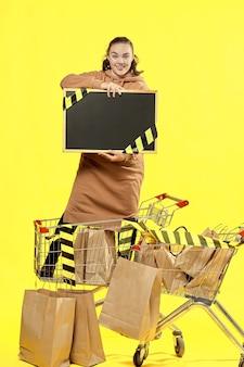 검은 금요일. 소녀는 쇼핑 카트에 복사할 장소가 있는 검은색 표지판을 들고 있습니다.