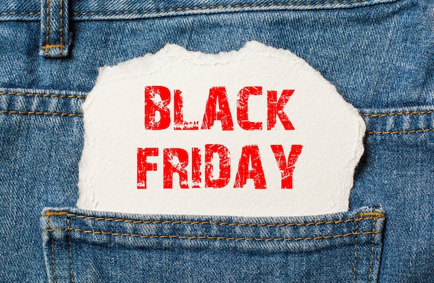Black friday on white paper in the pocket of blue denim jeans
