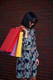 Черная пятница. женщина, держащая бумажные пакеты в руке. супермаркет.