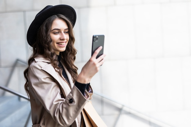 Black friday, woman using smartphone and holding shopping bag while standing on the mall wall