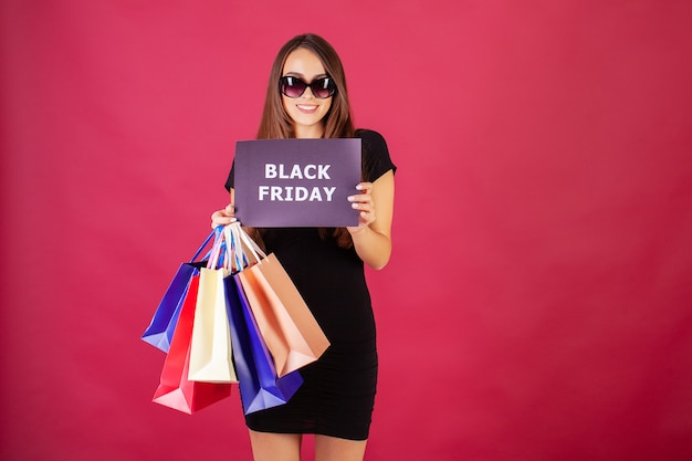 Black friday. woman with the inscription black friday and gift bags