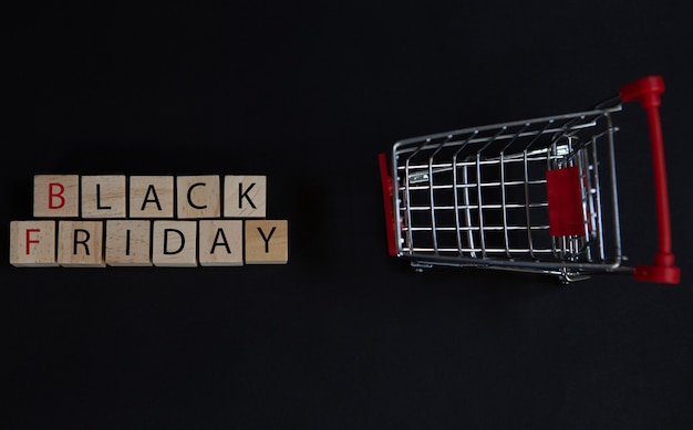 Black friday written on wooden cubes and a trolley