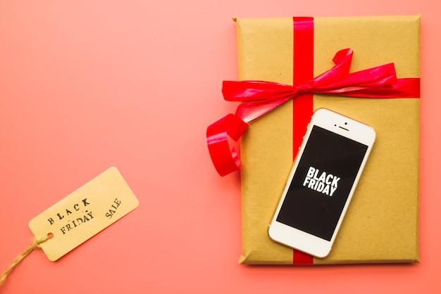 Подарочная коробка с надписью black friday на смартфоне