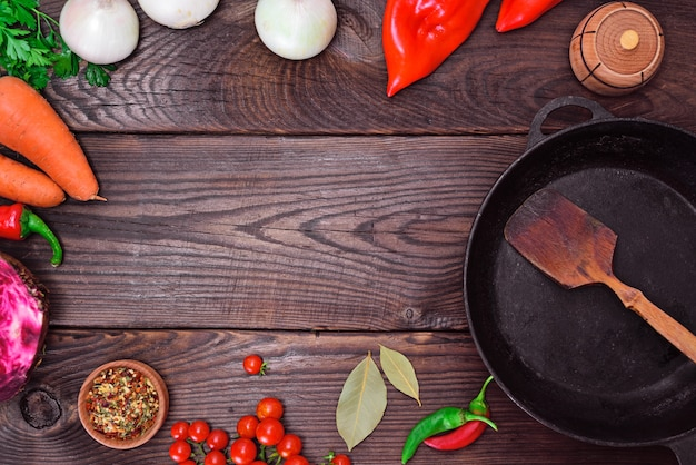 Black frying pan and fresh vegetables