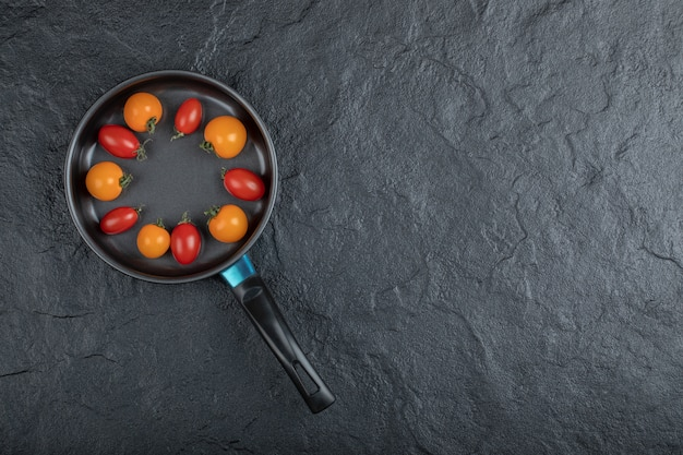Black frying pan full of cherry tomatoes. high quality photo