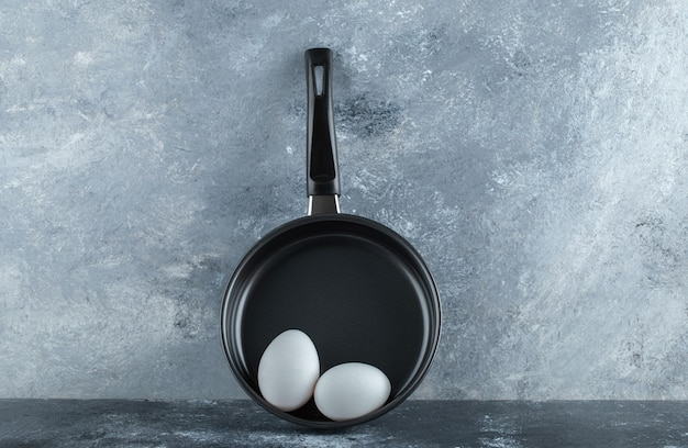 Black frying pan with two organic chicken eggs over grey table.