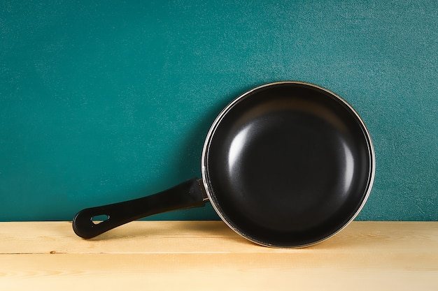 Black frying pan on a wooden shelf. kitchenware.