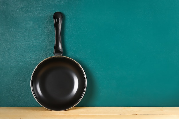 Black frying pan on a wooden shelf on teal background. kitchenware.
