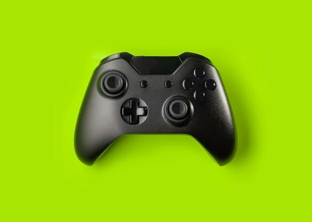 緑の背景に分離された黒のゲームコントローラー