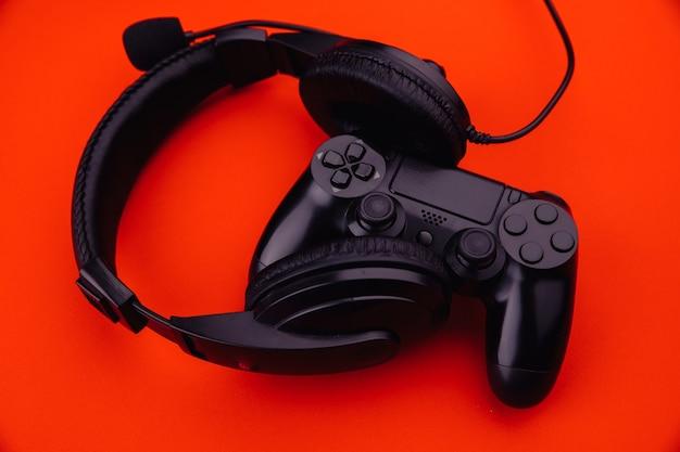 Черный геймпад и наушники, изолированные на красном фоне крупным планом. игровая концепция.