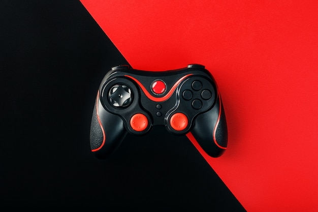 Black gamepad on a black red surface