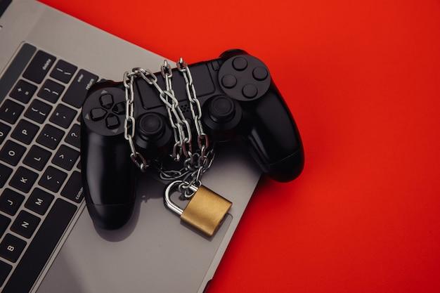 ノート パソコンにチェーンと南京錠が付いた黒いゲームパッド。