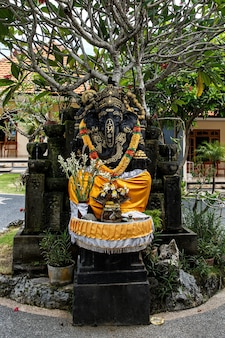 Black ganesha statue with a wreath of flowers.