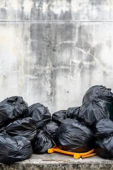 Black garbage bag  with old brick wall background