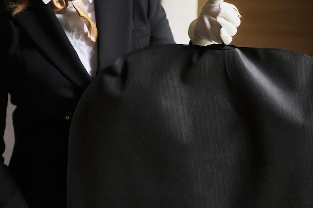 흰색 장갑을 낀 호텔 직원의 검은색 의류 정장 여행 가방