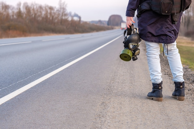 Black gas mask in the hand of a girl standing on the edge of a country highway
