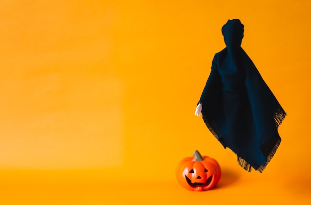 Black ghost sheet flying on orange background with blurred pumpkin on the floor. halloween minimal concept.