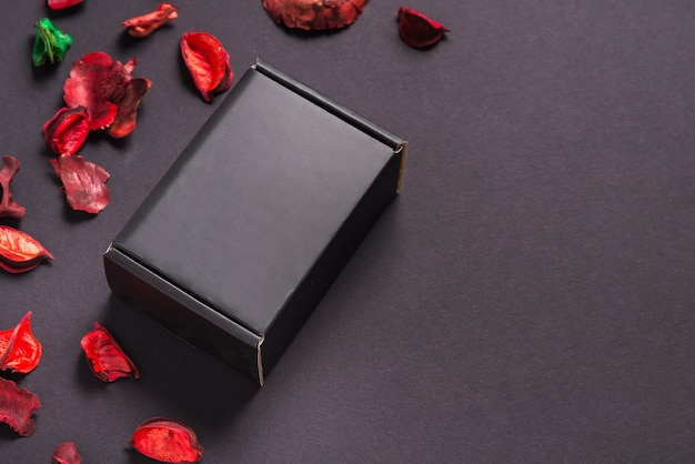 Black gift box and dry flowers on black surface