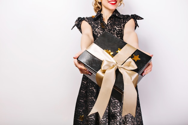 Black gift box in her hands, red lips, black dress, surprise emotion.