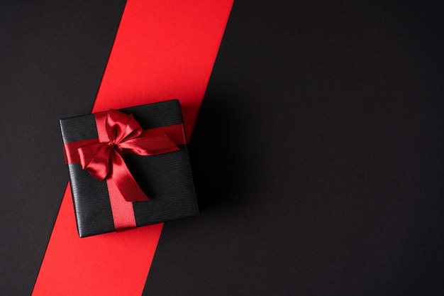 Черная подарочная коробка на темном контрастном фоне, украшенная ярким фактурным бантом. вид сверху
