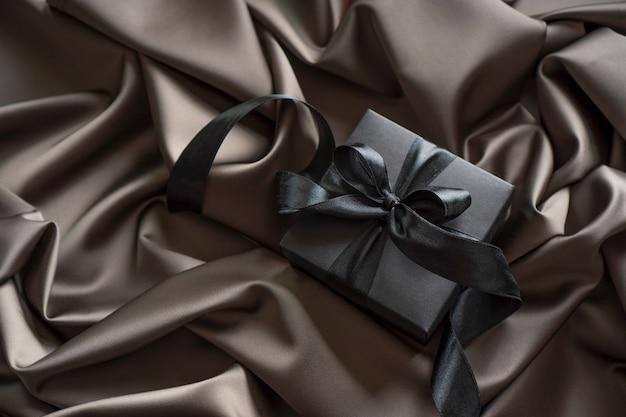 Черная подарочная коробка с черной лентой-бантом на атласном постельном белье.