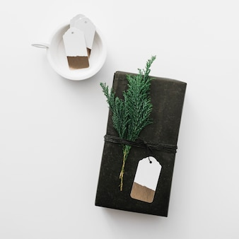 Black gift box with cypress branch on light table