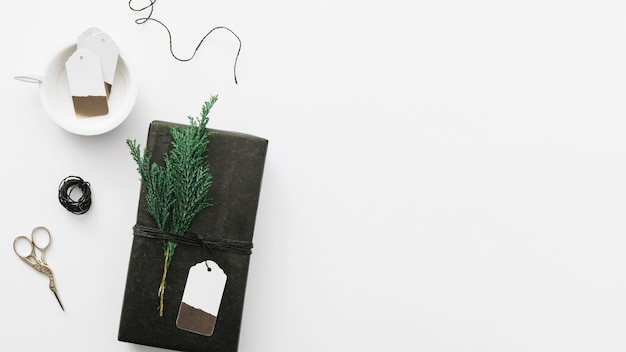 Black gift box with cypress branch on white table