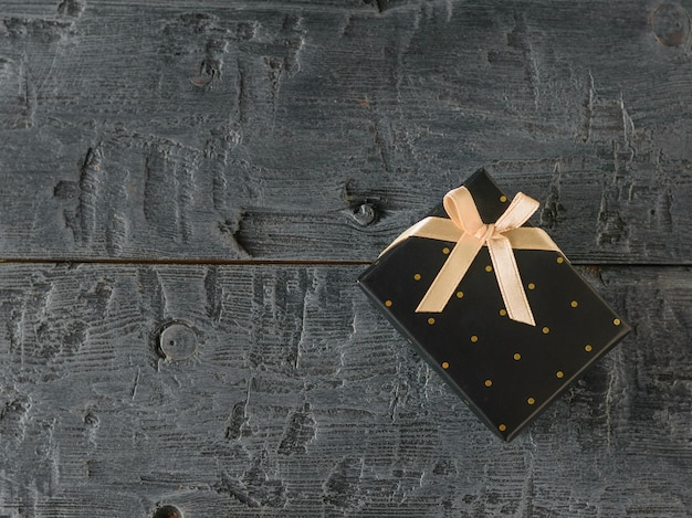 Black gift box with gold ribbon on black table