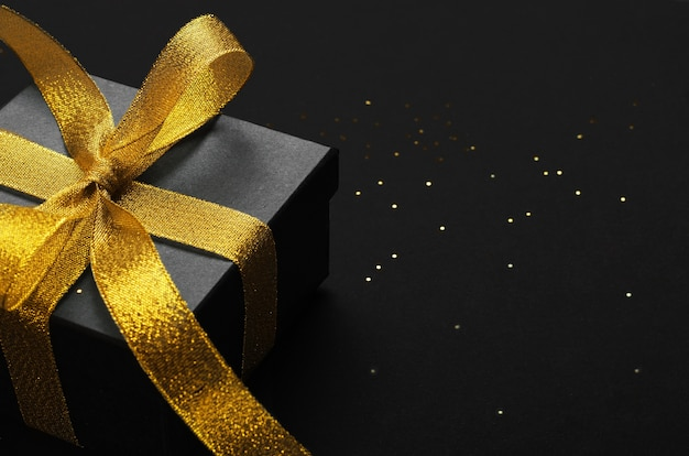 Black gift box with golden bow top view background.