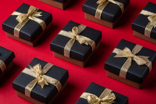 Black gift box with golden ribbons on red paper background, pattern, isolated, angle view
