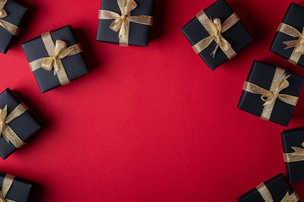 Black gift box with golden ribbons on red paper