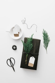 Black gift box with green cypress branch on white table