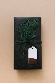 Black gift box with green cypress branch