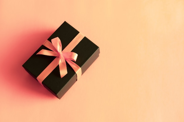 Black gift box with orange bow on pastel coral pink background. flat lay festive minimal style.