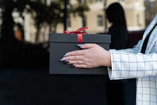 여성의 손에 붉은 활과 검은 선물 상자. 여자는 선물을 걸립니다. 닫기, 측면보기.